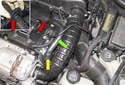 Working at the crankcase breather heater (yellow arrow), cut the plastic hose tie off the hose (green arrow).