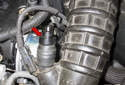 Working at the crankcase breather heater, install the hose adapter (red arrow) by pushing it into the valve opening.