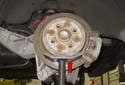 Support the wheel hub or brake rotor with a jack stand (red arrow).