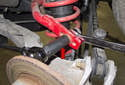 Working at the sway bar, loosen the 16mm end link nut (red arrow) while counter-holding the ball joint with a 16mm or 18mm wrench or vise grips.