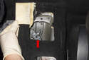 Lift the carpet panel at the rear of the center tunnel to expose the parking brake lever cables and bracket (red arrow).