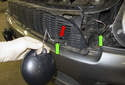 If you have fog lights, disconnect the electrical connector (green arrow).