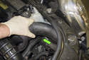 Working at the left side of the engine compartment, pull the intake air duct (green arrow) out of the radiator support.