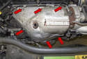 Working at the turbocharger heat shield, remove the six 10mm fasteners (red arrows).