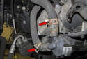 Working at the auxiliary coolant pump, use hose clamp pliers to loosen the hose clamps, then remove the hoses from the pump (red arrow).