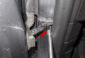 Working at the door jamb, remove the E10 inverted Torx fastener (red arrow).