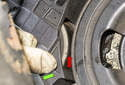 To check for a weak internal tension spring, pull the friction wheel away from the crankshaft pulley (green arrow).