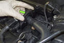 Working at the left side of the valve cover, lift up to detach the hose lock (green arrow) at the valve cover.