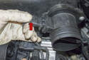 Working at the mass airflow sensor, disconnect the electrical connector (red arrow).