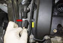 Working at the right side of the valve cover, unplug the charge air duct sensor electrical connector (red arrow).