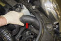 Move to the left side of the radiator support and remove the fresh air duct (red arrow).