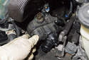 Slide the small hose off the thermostat and remove the thermostat from the engine.