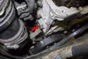Working at the rear right of the cylinder head, remove the timing chain tensioner (red arrow).