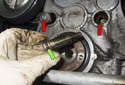 Working just above the crankshaft pulley hub, remove the two timing chain guide fasteners (red arrows).
