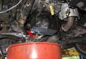 Drain the engine oil (red arrow).