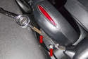 Working at the top of the steering column, remove the two T30 Torx fasteners (red arrows).