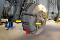 With the wheel off you can see the brake caliper (red arrow) along with the two brake pads, one on each side of the rotor (yellow arrows, one shown).