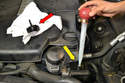 Clean around the cap of the power steering reservoir (red arrow) so you do not get any dirt into the power steering system and then remove the cap.