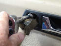 Remove the door pull handle trim piece and unscrew the 10mm nut behind it.