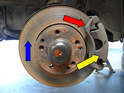 This photo shows the brake rotor (blue arrow), caliper mount (red arrow) and the caliper (yellow arrow).