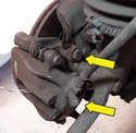 Remove the two mounting bolt connecting the caliper assembly to the upright (yellow arrows, only top one shown).