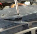 Remove the Phillips-head screw that holds the ambient air sensor to the lower part of the license plate frame.