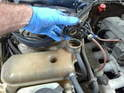 Remove the coolant tank cap to break the vacuum seal in the system.