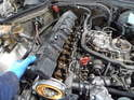 Remove the vacuum hose from the valve cover and the eight 10mm bolts holding the valve cover on.