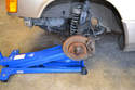 With the car safely supported off the ground, place a floor jack under the control arm.