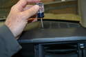 Using a small Phillips-head screwdriver, remove the two screws on both the driver and passenger side speaker covers.
