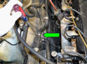 Using a flathead screw driver, loosen the clamp and remove the return hose (green arrow) by the recirculation pump.
