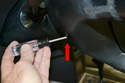 Use a T-30 and loosen both screws that hold the airbag unit on (red arrow).