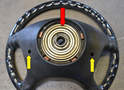 On the back side of the steering wheel you can see the horn and airbag contact rings (red arrow) and the access points for the T-30 screws (yellow arrows).