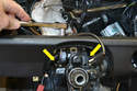 Use a 13mm socket and extension to remove the two bolts holding the steering main shaft to the dash brace (yellow arrows).
