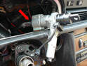 Working underneath the dash, remove the two 10mm nuts connecting the steering shaft to a cross brace (red arrows).