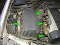 To remove the old filter element, open the hood and locate the clips securing the airbox cover to the airbox (green arrows).
