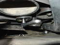Locate the serpentine belt tensioner to the left of the radiator fan.