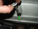 Shown here is a new grommet for the valve cover retaining bolts installed in the valve cover (green arrow).