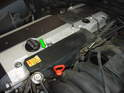 Begin by pulling the protective cover off the valve cover to the rear of the fuel pressure regulator (green arrow).