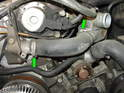 Loosen and remove the two hose clamps holding the water hose going from the water pump to the engine block.
