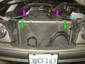 Reconnect the two 10mm bolts holding the A/C condenser to the radiator (green arrows) along with the two small spring clips that hold the fan shroud to the radiator (purple arrows).