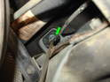 Use a screwdriver to push the old bushing out of the end of the gear selector lever (green arrow).