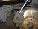 With the caliper guide bolts and retaining spring removed, you should be able to lift the caliper off its bracket.