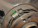 Spread the brake shoes apart at the top and remove the adjuster screw (green arrow) Use extreme caution as the springs hold everything together very tight.