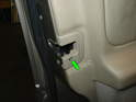 To remove the door panel, begin by removing the screw holding the door latch cover in place (green arrow).