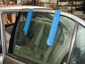 The first step in removing the rear window regulator is to tape the window up around the door frame as shown here.