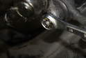 Using a 17mm wrench, loosen and remove the crown bolt.