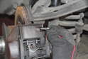 Remove the bleeder screw cap located on the brake caliper.