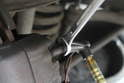 Using a 9mm open end line wrench, turn the bleed screw clockwise to open the flow of brake fluid.