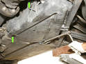 A plastic shield covers the fuel pump and filter in front of the rear suspension on the left side rear tire.